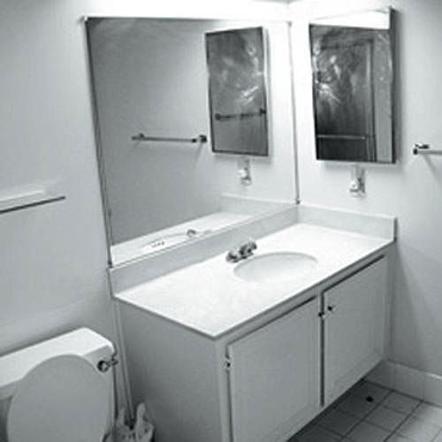 black and white photo of a plain bathroom with a sink in a simple cabinet with a wall mirror above