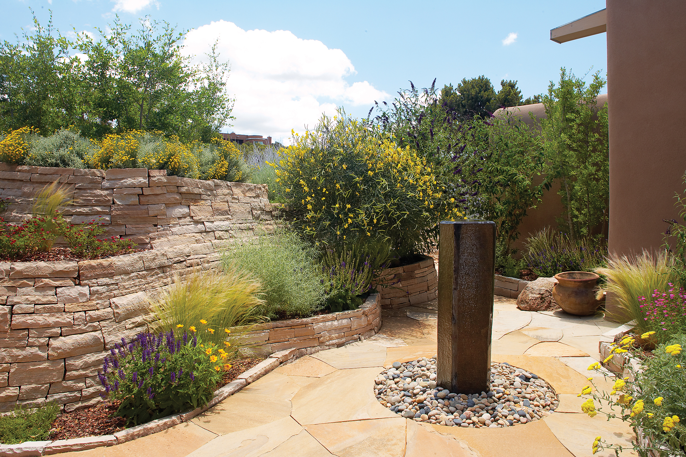 49 landscaping ideas with stone sunset magazine for Fountain grass landscaping ideas
