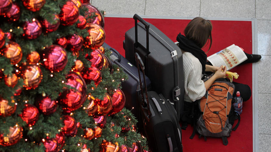 Airport traveler beside Christmas tree