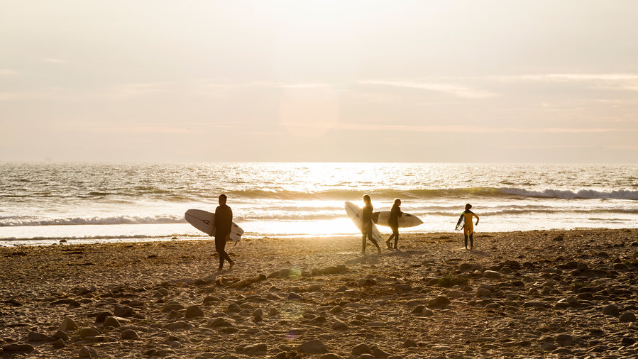 Surfers walking on the beach at sunset in San Buenaventura State Beach in Ventura, California