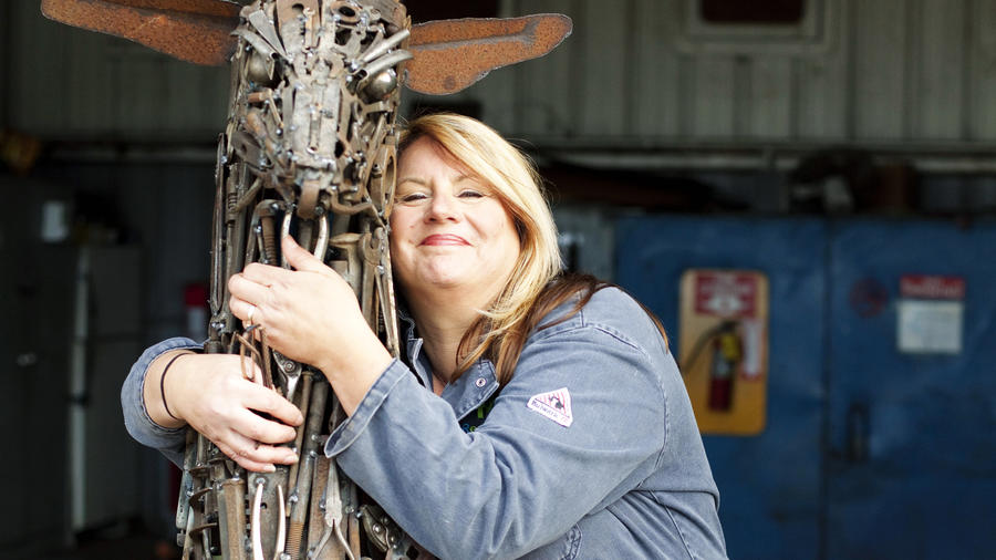woman hugging sculpture of an elk in Eureka, California, one of the best places to live in the West