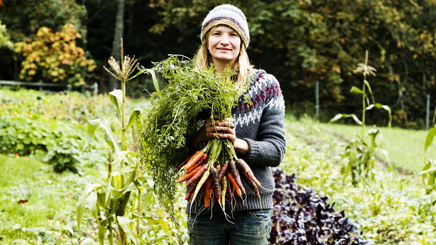 Woman holding carrots in her farm in Salt Springs Island, one of the best places live in the West