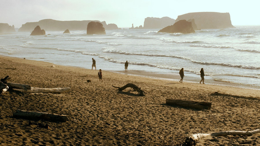 beach towns on the west coast bandon, oregon people walking on beach