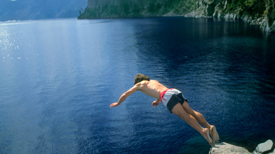 Best lake vacation Crater Lake with boy jumping off a rock into the water