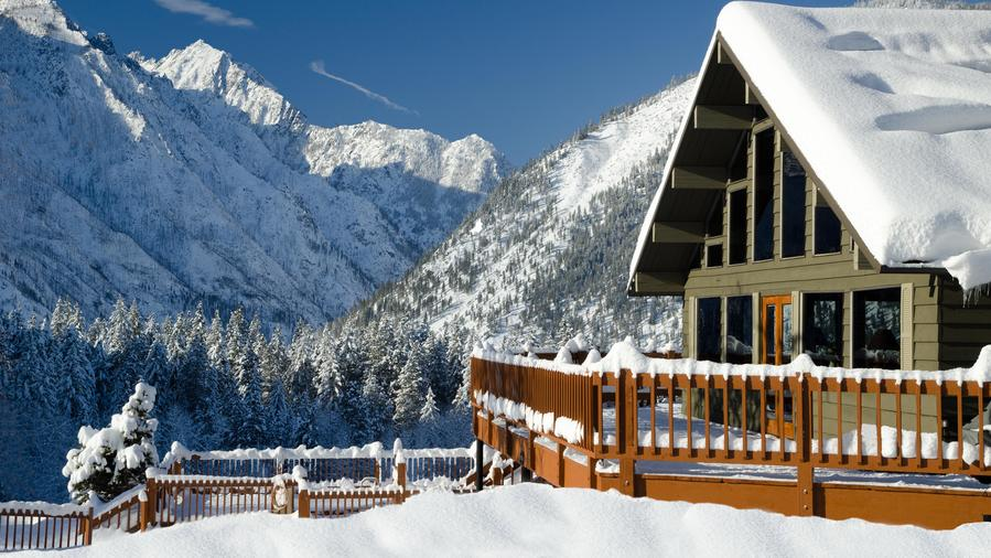 The exterior of Mountain Home Lodge in Washington, covered in snow during the day