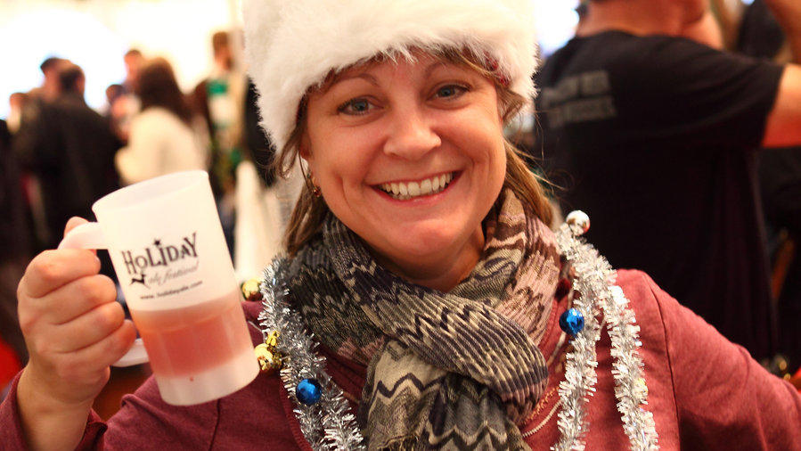 Woman holding beer while wearing Santa hat at Holiday Ale Festival in Portland
