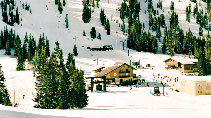 A small building surrounded by snow-covered mountain in Alta Ski