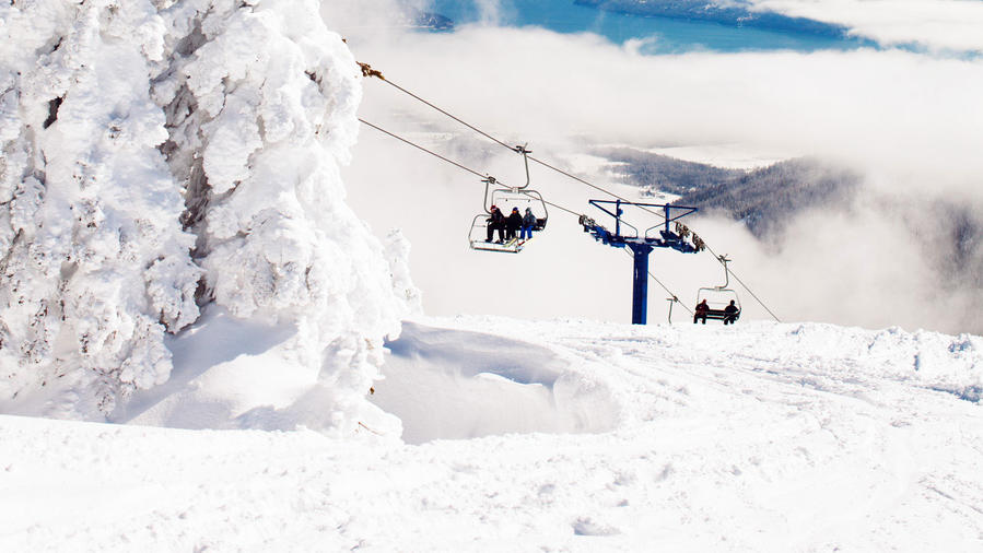 Trees and mountain covered in snow with chairlift in background at Schweitzer Mountain