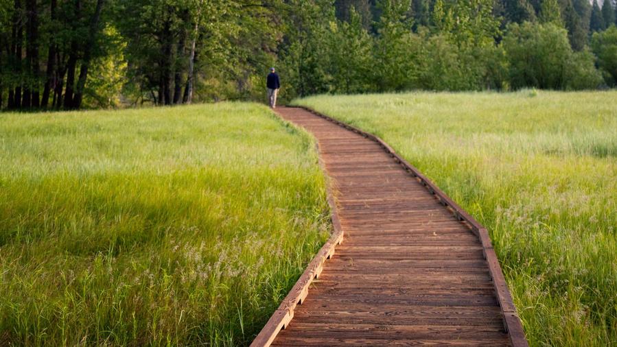 Man Walking on Path infront of Upper Yosemite Fall