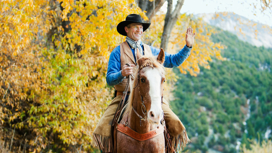 Man riding horse in Arroyo Seco with fall foliage in the background