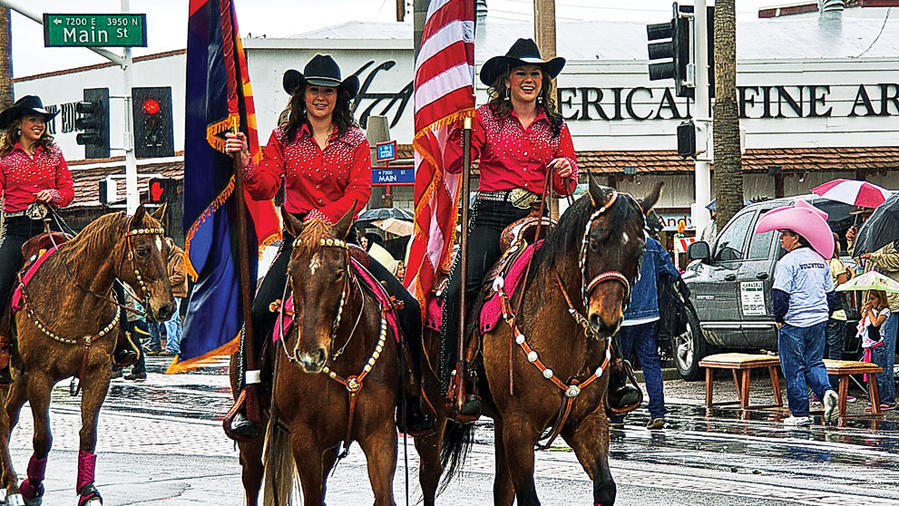 Two women riding horses in cowboy attire in Scottsdale parade