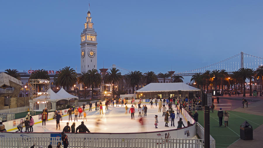 People ice skate under the Ferry Building's stunning white clock tower and the sprawling Bay Bridge
