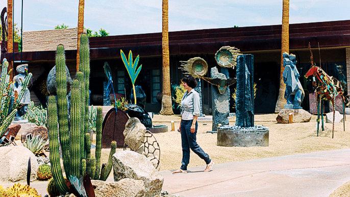Woman walking through an outdoor sculpture garden at the Desert Art Collection Garden in Palm Desert, CA