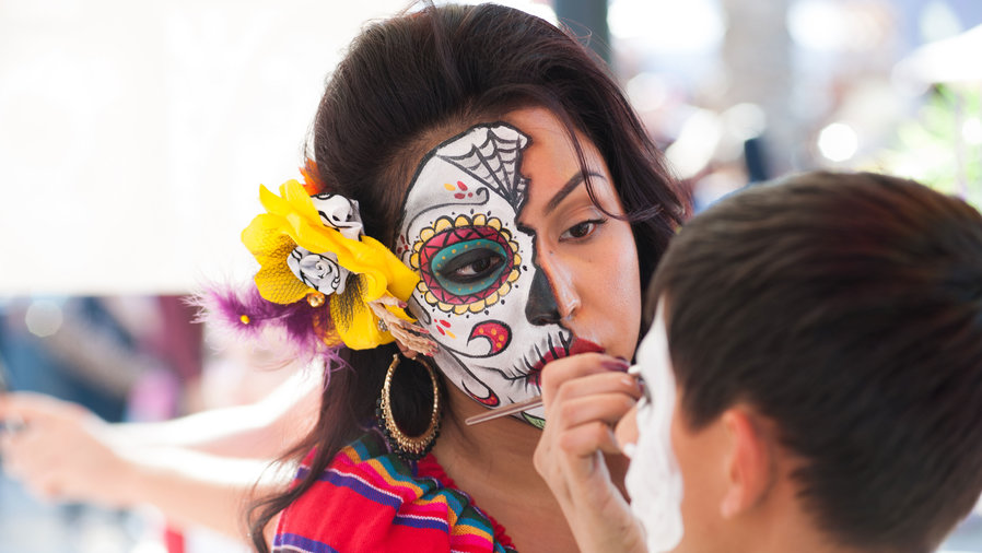Woman painting little boy's face for Dia de los Muertos Halloween events in Mesa, Arizona