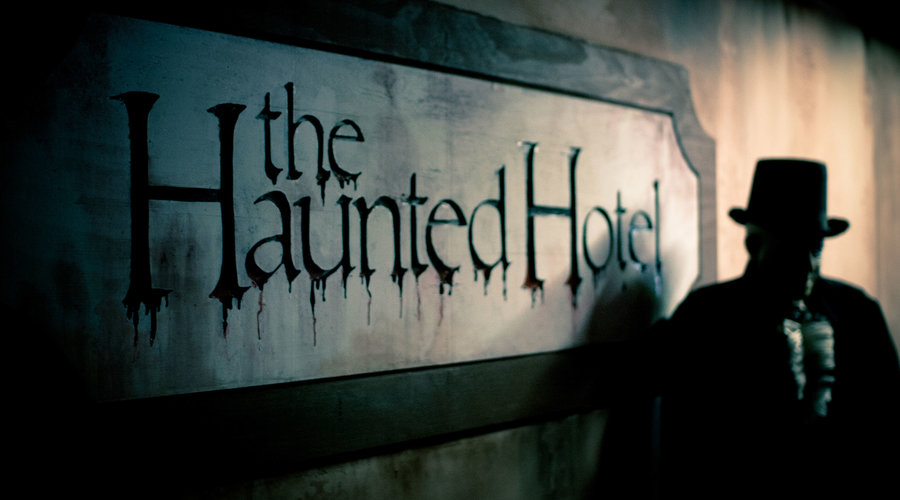 Man standing next to the Haunted Hotel haunted house in San Diego