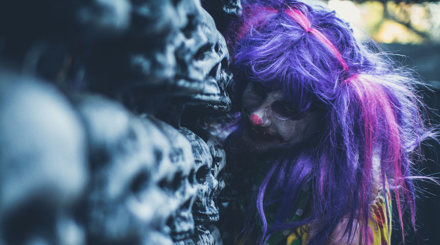 Creepy girl with purple hair standing in front of skulls at haunted houses in San Diego