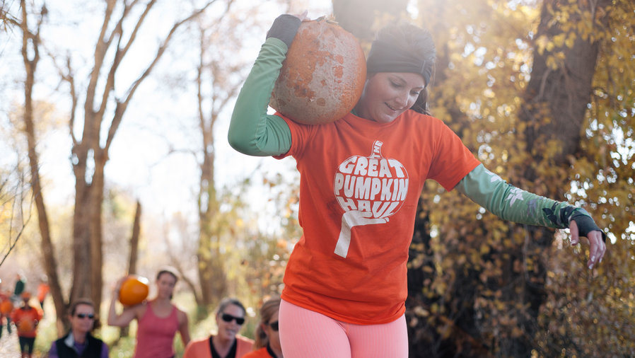 Woman carrying pumpkin on her shoulder at the Pumpkin Obstacle Race in Littleton, CO