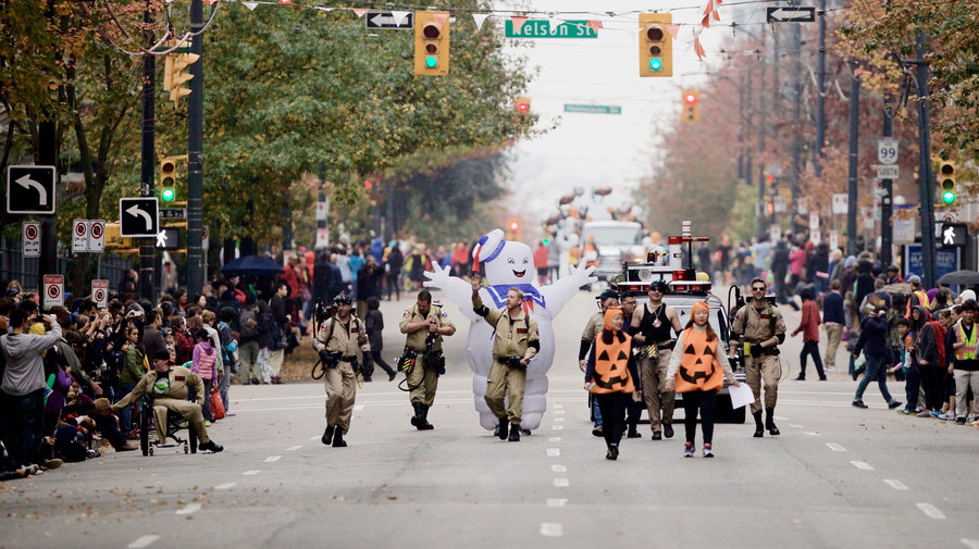 People in Ghost Busters costumes walking down the street in Vancouver for a parade, one of the city's Halloween events