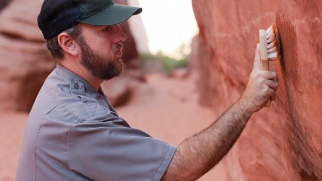 At Arches National Park, ranger Stephen Allen removes graffiti.  (NPS Photo by Andrew Kuhn)
