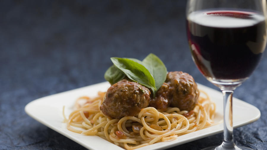 Close-up of spaghetti and meatballs with red wine