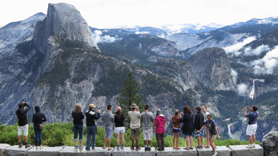 YOSEMITE NATIONAL PARK, CA - JULY 20: Visitors look out at Yosemite National Park from Glacier Point on July 21, 2014 in Yosemite National Park, California. Yosemite is among California's biggest tourist destinaitons. (Photo by Sean Gallup/Getty Images)