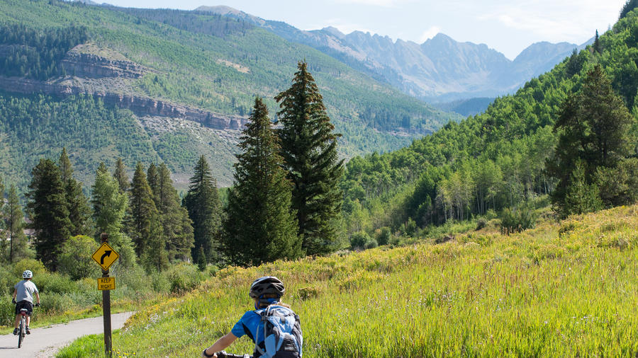Cyclists pedal beneath the Gore Range surrounding Vail, CO. (Photo by Ashley Davis Tilley.)
