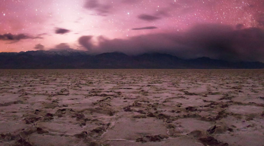 A pink sky covered in stars at Death Valley in winter